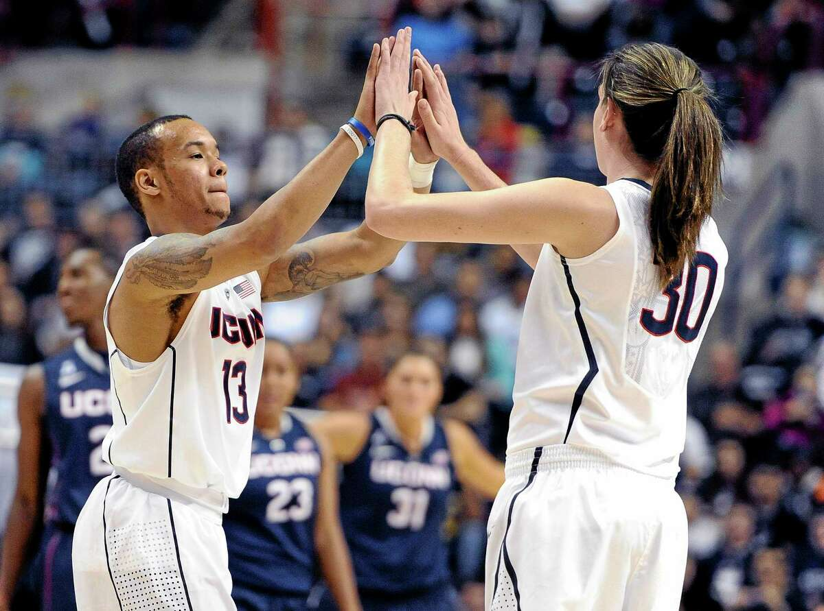 UConn's Shabazz Napier, left, high-fives teammate Breanna Stewart during an inter-squad scrimmage at the men's and women's basketball teams' First Night event in Storrs on Friday.