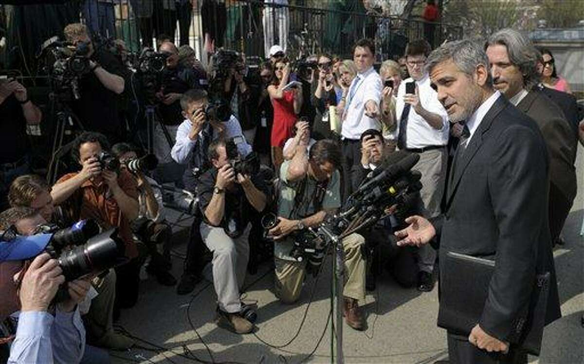 Actor George Clooney, accompanied by activist John Prendergast of the Enough Project, right, speaks to reporters outside the White House in Washington, Thursday after a meeting with President Barack Obama. Associated Press