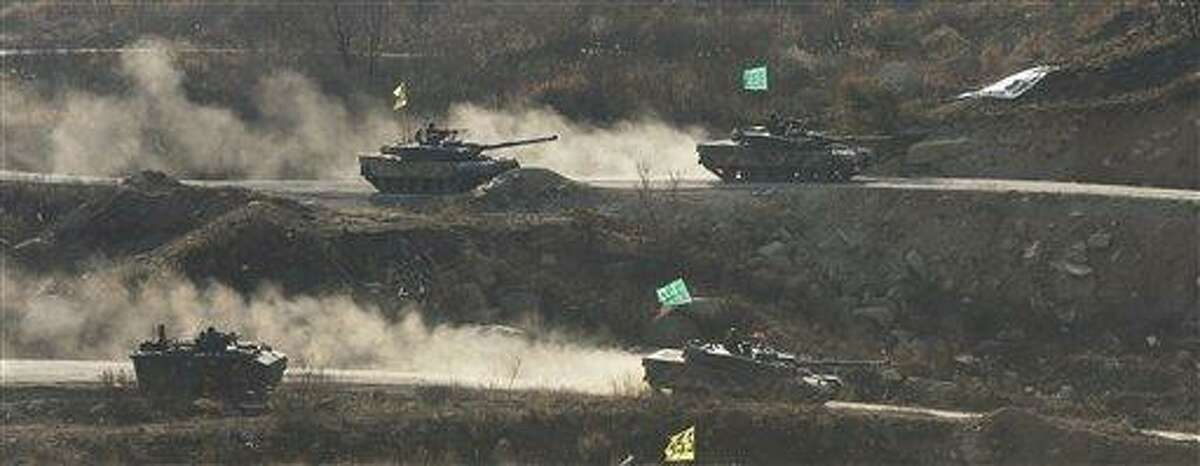 South Korean army K1 tanks move during an exercise at Seungjin Fire Training Field in mountainous Pocheon, South Korea, near the border with North Korea, Wednesday, March 27, 2013. North Korea said Wednesday that it had cut off a key military hotline with South Korea that allows cross border travel to a jointly run industrial complex in the North, a move that ratchets up already high tension and possibly jeopardizes the last major symbol of inter-Korean cooperation. (AP Photo/Yonhap, Lim Byung-shick)