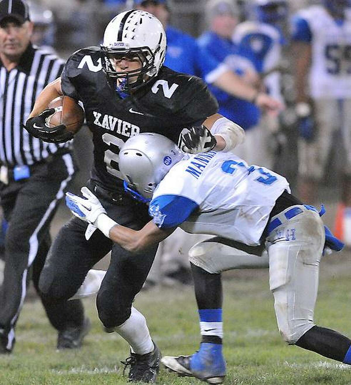 Middletown-- Xavier's Joseph Carbone takes the hit from West Haven's Jawaun Manning after a short gain during the third quarter. Photo--Peter Casolino/New Haven Register. 11/12/12