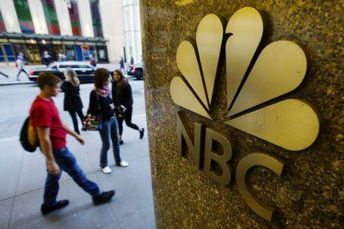Pedestrians walk past an NBC logo outside Rockefeller Center in New York April 30, 2013. Comcast's quarterly result was hurt by the struggles of its broadcast network, NBC. It beat Wall Street's earnings expectations, however, though that was driven by strength in other segments of the media business. Picture taken April 30, 2013. REUTERS/Lucas Jackson (UNITED STATES - Tags: BUSINESS LOGO MEDIA)