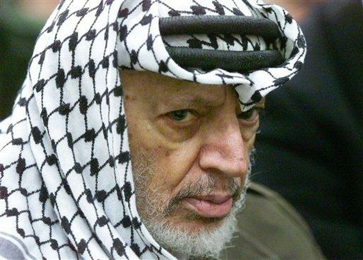 In this 2002 file photo, Palestinian leader Yasser Arafat pauses during the weekly Muslim Friday prayers in his headquarters in the West Bank city of Ramallah. Yasser Arafat's body may be exhumed to allow for more testing for the causes of his death, after a Swiss lab said it found elevated levels of a radioactive isotope in belongings the Palestinian leader is said to have used in his final days. Associated Press