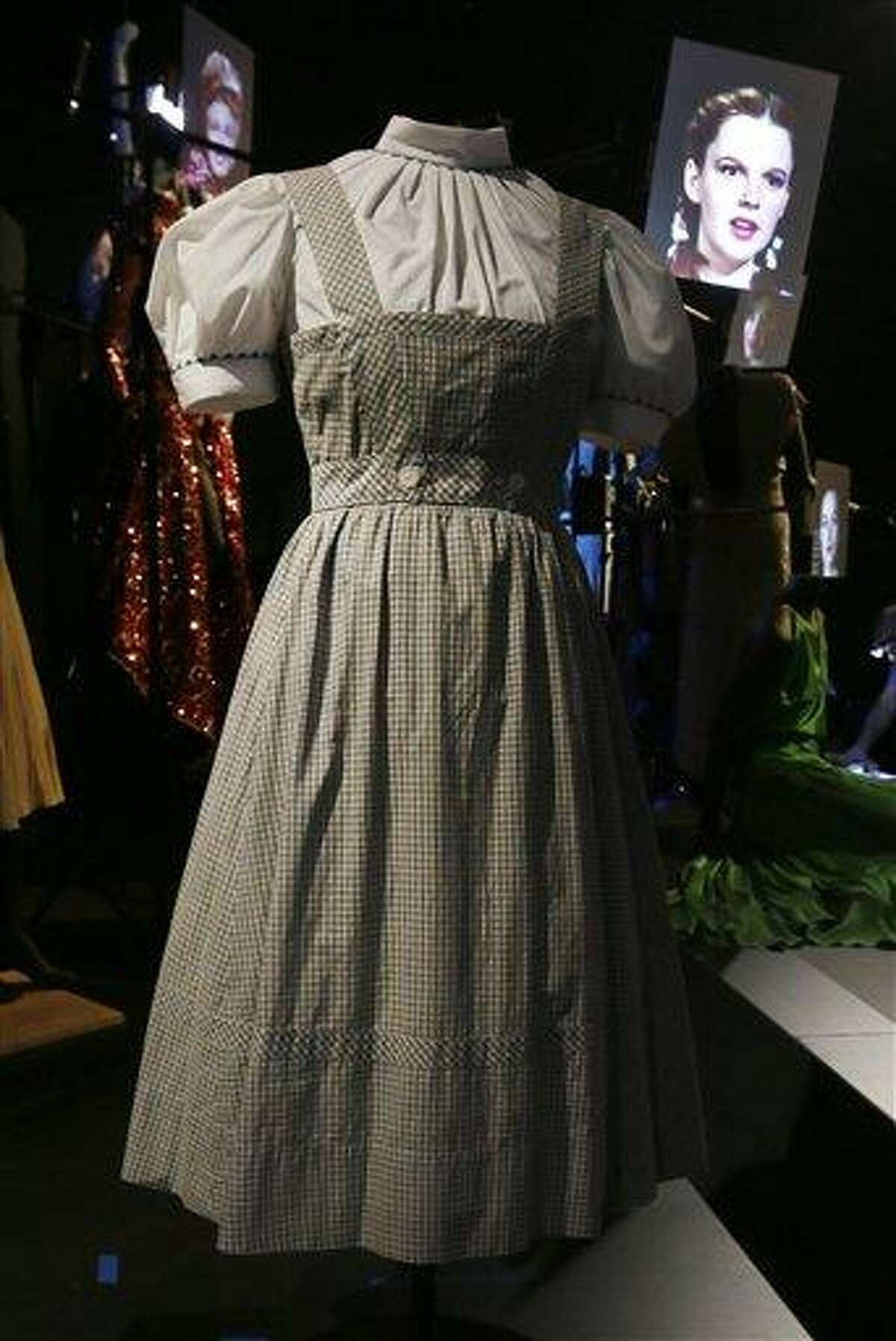 The blue and white gingham pinafore dress worn by Judy Garland in her iconic role of Dorothy designed by Adrian for the 1939 film The Wizard Of Oz, with a video portrait of garland in the background, on display at the Hollywood Costume exhibition at the Victoria and Albert Museum in London. The show showcases more than one hundred movie costumes from a century of film-making. The exhibition opened to the public Oct. 20, 2012 and runs till 27 Jan. 2013. AP Photo/Alastair Grant