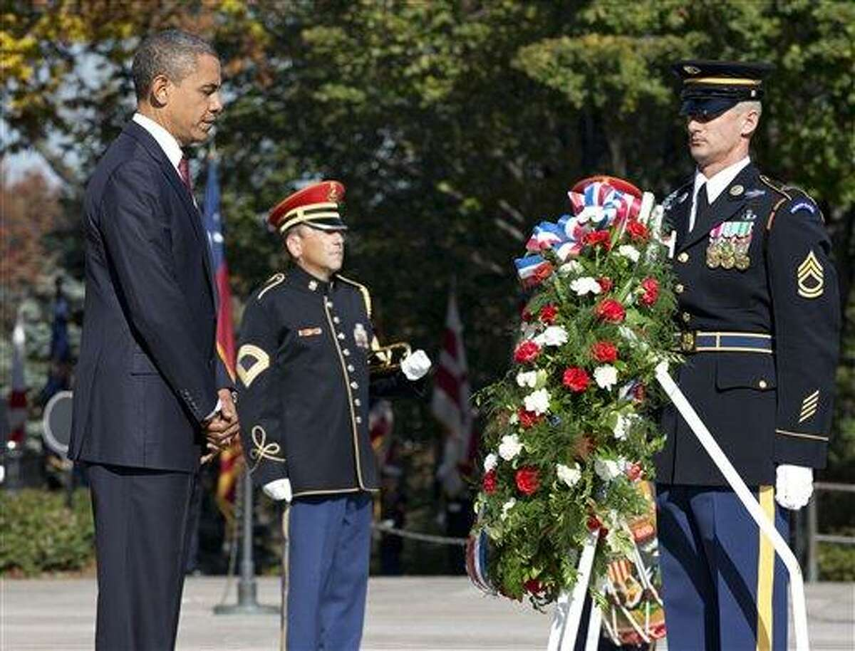 President Barack Obama presents a wreath at the Tomb of the Unknowns at Arlington National Cemetery during a Veterans Day ceremony in Arlington, Va. Sunday. AP Photo/J. Scott Applewhite