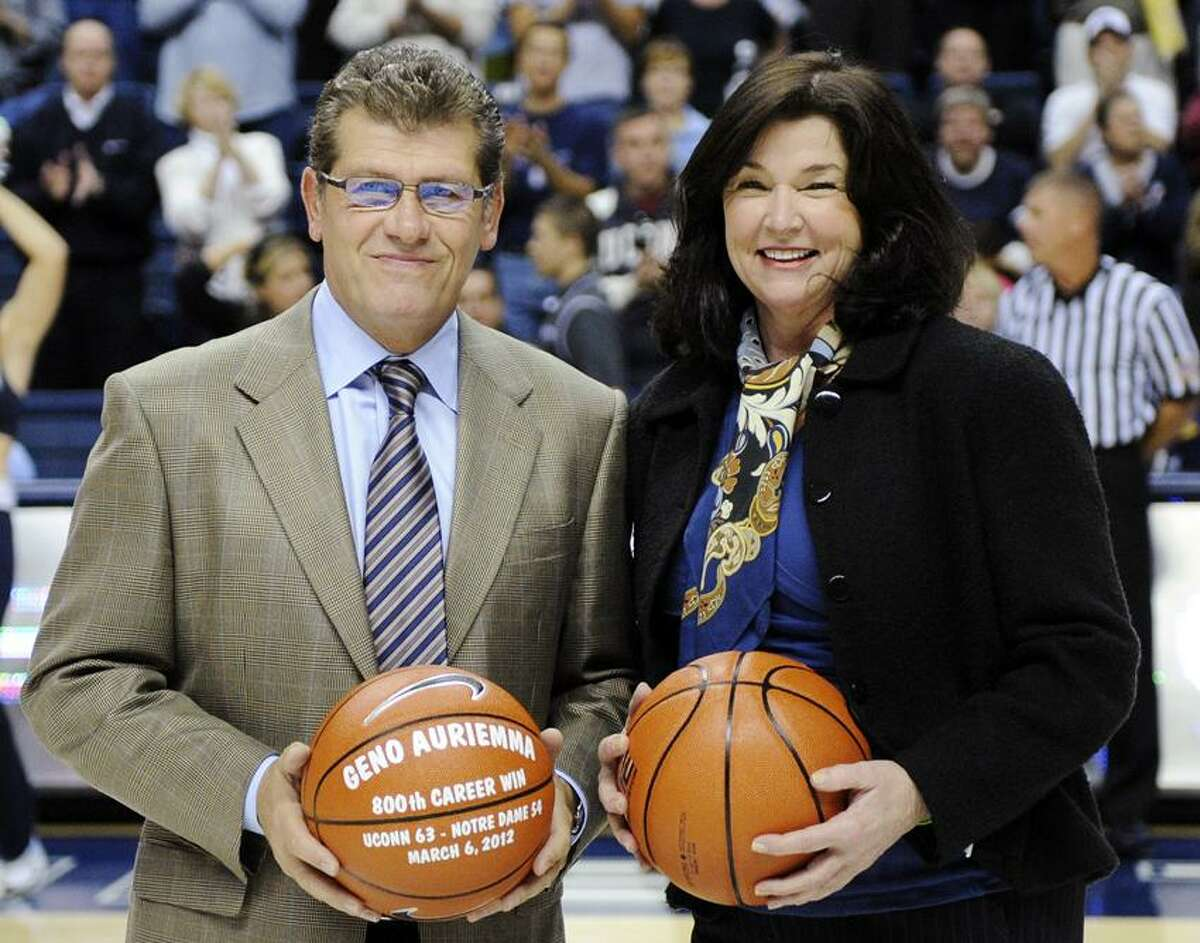 Connecticut senior associate director of athletics Debbie Corum, right, smiles after presenting a commemorative basketball to head coach Geno Auriemma celebrating his 800th career win before his team's NCAA college basketball game against Charleston in Storrs, Conn., Sunday, Nov. 11, 2012. (AP Photo/Fred Beckham)
