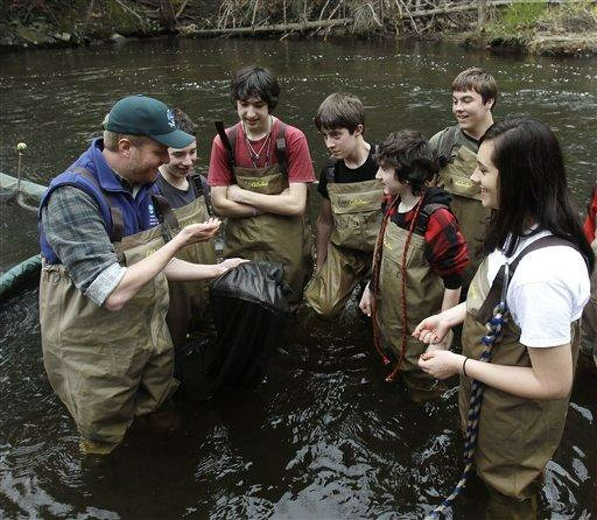 In this April 2011 file photo, Chris Bowser of the New York State Department of Environmental Conservation, left, checks a net for American eels with Kingston High School students on the Black Creek in West Park, N.Y. They have a reputation for being environmentally minded do-gooders. But an academic analysis of surveys spanning more than 40 years has found that today's young Americans are less interested in the environment and in conserving resources - and often less civic-minded overall - than their elders were when they were young. Associated Press
