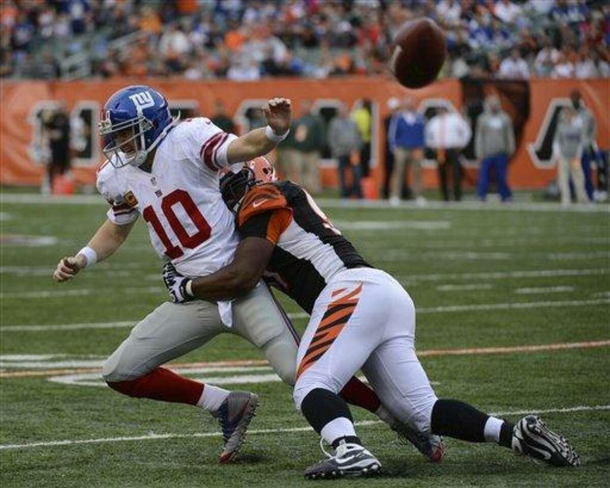 New York Giants quarterback Eli Manning (10) is pursued by Cincinnati Bengals defensive tackle Geno Atkins in the second half of an NFL football game, Sunday, Nov. 11, 2012, in Cincinnati. (AP Photo/Michael Keating)