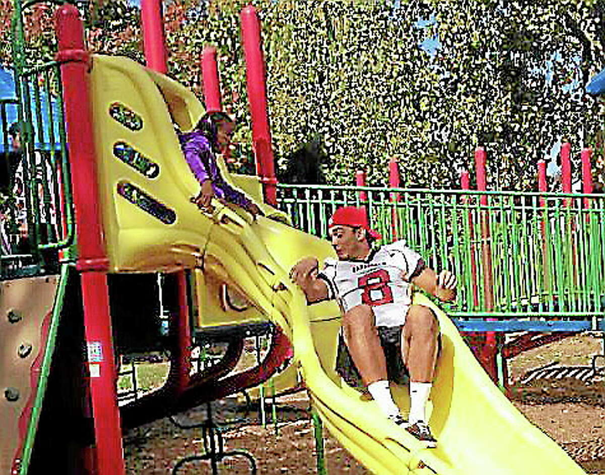 Devon Carrillo, a Wesleyan football player, slides down the slide in front of a Macdonough student during recess Oct. 18.