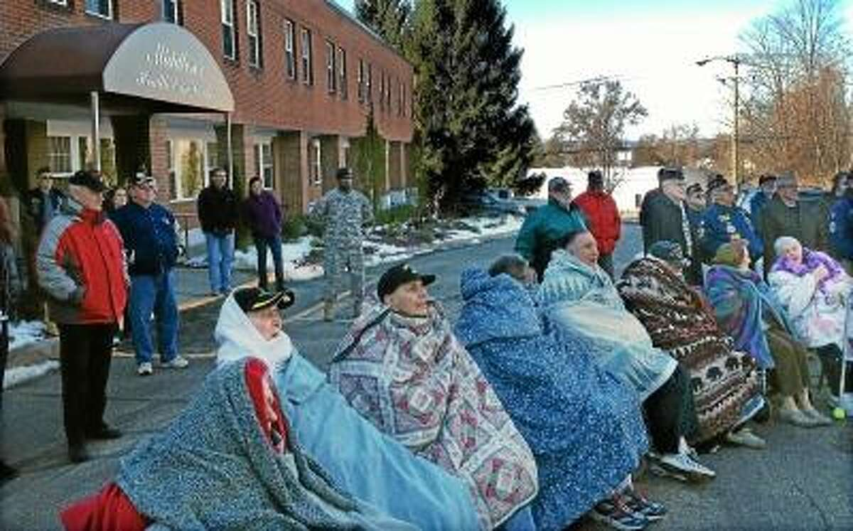 Veteran residents at the Middlesex Health Care Center sit outside wrapped in blankets during a cold morning to watch a flag raising ceremony in honor of Veteran's Day. Photo by Lauren Sievert/ The Middletown Press