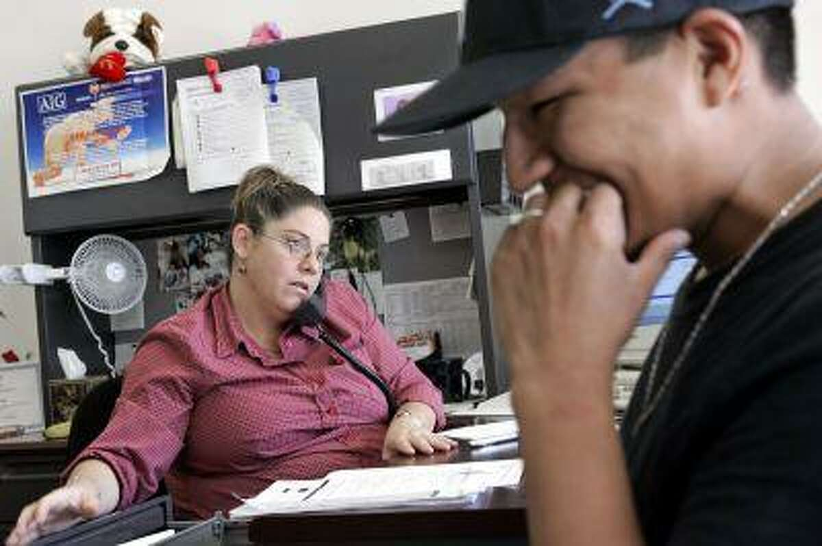 Ayesha Tully, left, responds to call while Larryll Emerson waits for information pertaining to his next work assignment, in this file photo from July 26, 2005, at the Staffmark temp agency in Cypress, Calif. (AP Photo/Ric Francis)