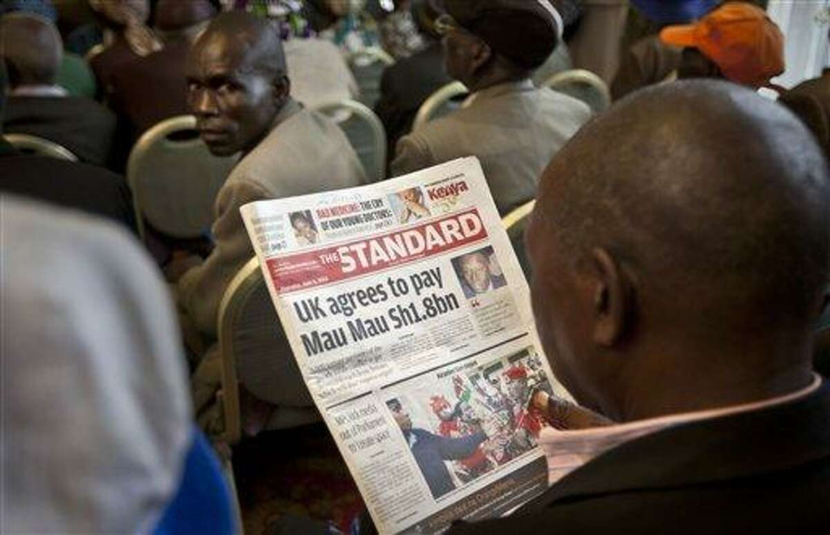 """A Kenyan man reads a copy of Kenya's The Standard newspaper as Mau-Mau veterans await a press conference about an announcement regarding their legal case for compensation against the British Government, in Nairobi, Kenya Thursday, June 6, 2013. Several thousand now-elderly Kenyans say they were beaten and sexually assaulted by officers acting for the British administration trying to suppress the """"Mau Mau"""" rebellion, in which groups of Kenyans attacked British officials and white farmers who had settled in some of Kenya's most fertile lands. (AP Photo/Ben Curtis)"""