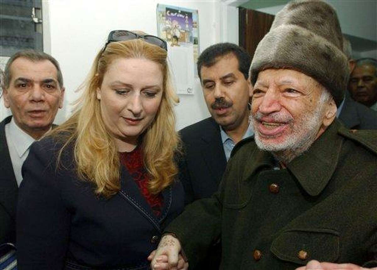 In this 2004 file photo, Palestinian leader Yasser Arafat and his wife Suha hold hands prior to Arafat's departure from his compound in the West Bank town of Ramallah. Arafat's body may be exhumed to allow for more testing of the causes of his death, the Palestinian president said Wednesday after a Swiss lab said it found elevated levels of a radioactive isotope in belongings the Palestinian leader is said to have used in his final days. Associated Press
