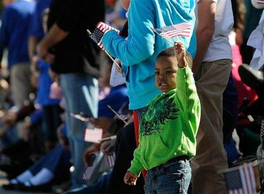 James Collier III, 2, waves a U.S. flag as the 31st annual Veterans Day Parade makes its way through downtown Atlanta, Saturday, Nov. 10, 2012. (AP Photo/David Tulis) Photo: AP / FR170493 AP