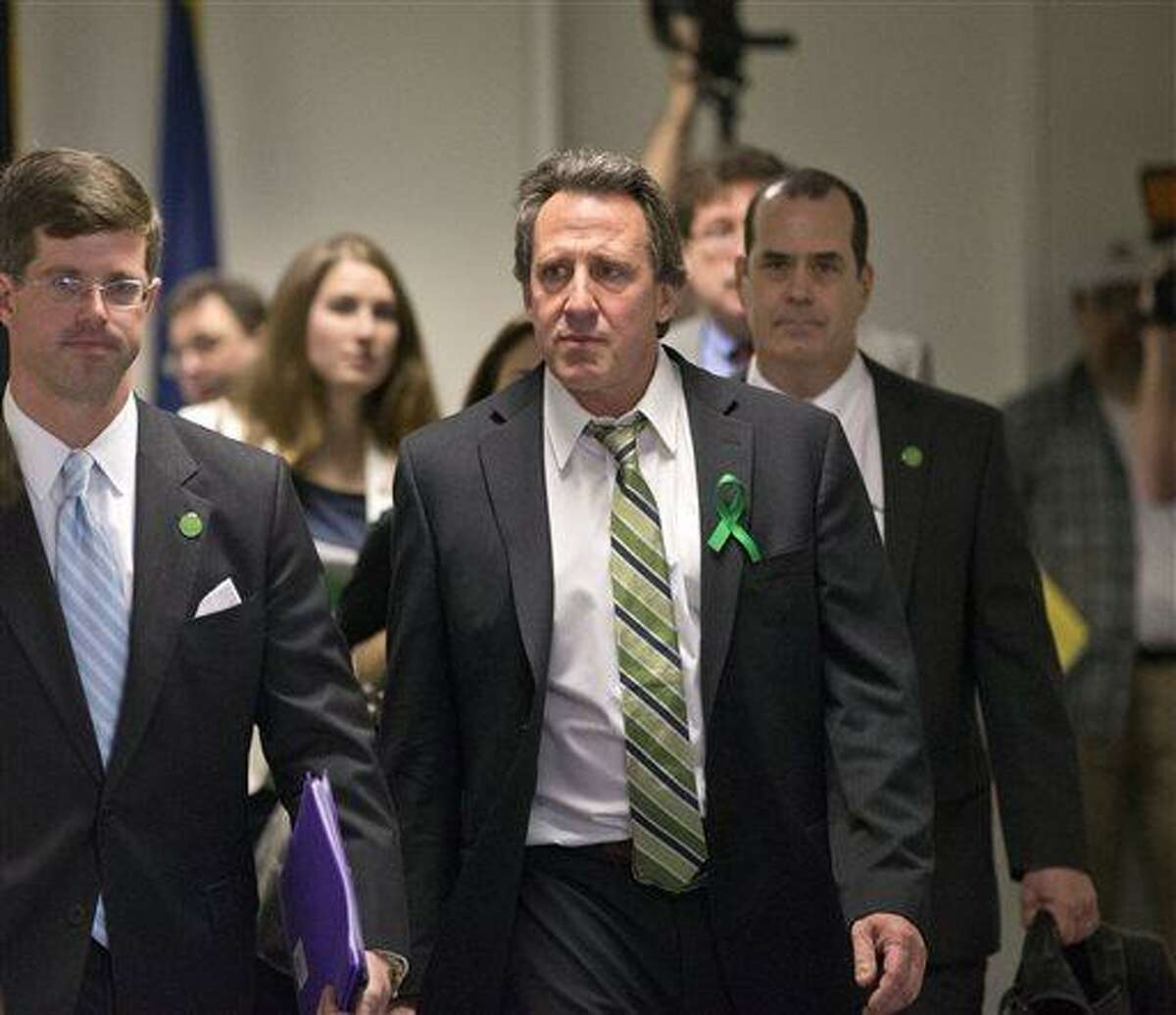 FILE - In a Tuesday, April 9, 2013 file photo, Neil Heslin, center, whose 6-year-old son Jesse was killed in the mass shooting in Newtown, Conn., arrives with other victims' families to meet privately with senators on Capitol Hill in Washington. Heslin was scheduled to appear in Connecticut Superior Court Wednesday, May 8, 2013 on larceny and other charges. Heslin had five separate cases listed on the docket in Milford Superior Court. He has pleaded not guilty to all the charges. (AP Photo/J. Scott Applewhite)
