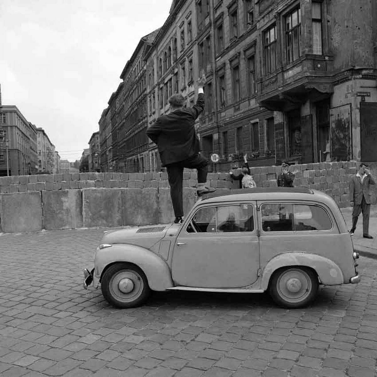 Stone wall doesnít stop curious West Berliners from viewing the Eastern part of the city. Communists put up wall to keep people in the Eastern sector. An auto-mobile used by man to overcome height of problem in Berlin August 28, 1961. (AP Photo/Worth)
