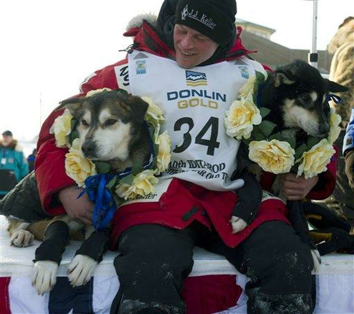 Dallas Seavey holds his leaders, Diesel, left, and Guiness after he arrived at the finish line to claim victory in the Iditarod Trail Sled Dog Race in Nome, Alaska, Tuesday. Seavey is the youngest musher to win the nearly 1,000-mile race across Alaska. Associated Press