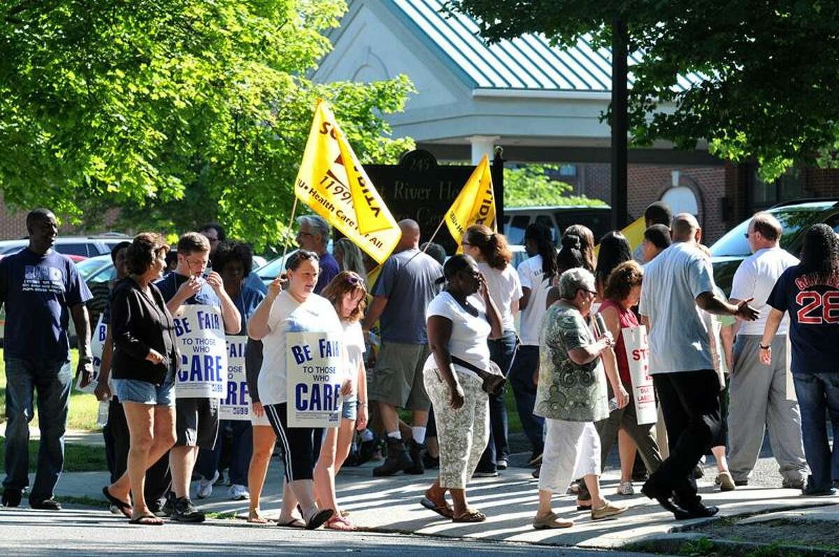 Caregivers strike outside the West River Health Care center Tuesday in Milford, one of five sites in the state where workers picketed over alleged unfair labor practices. Peter Casolino/New Haven Register