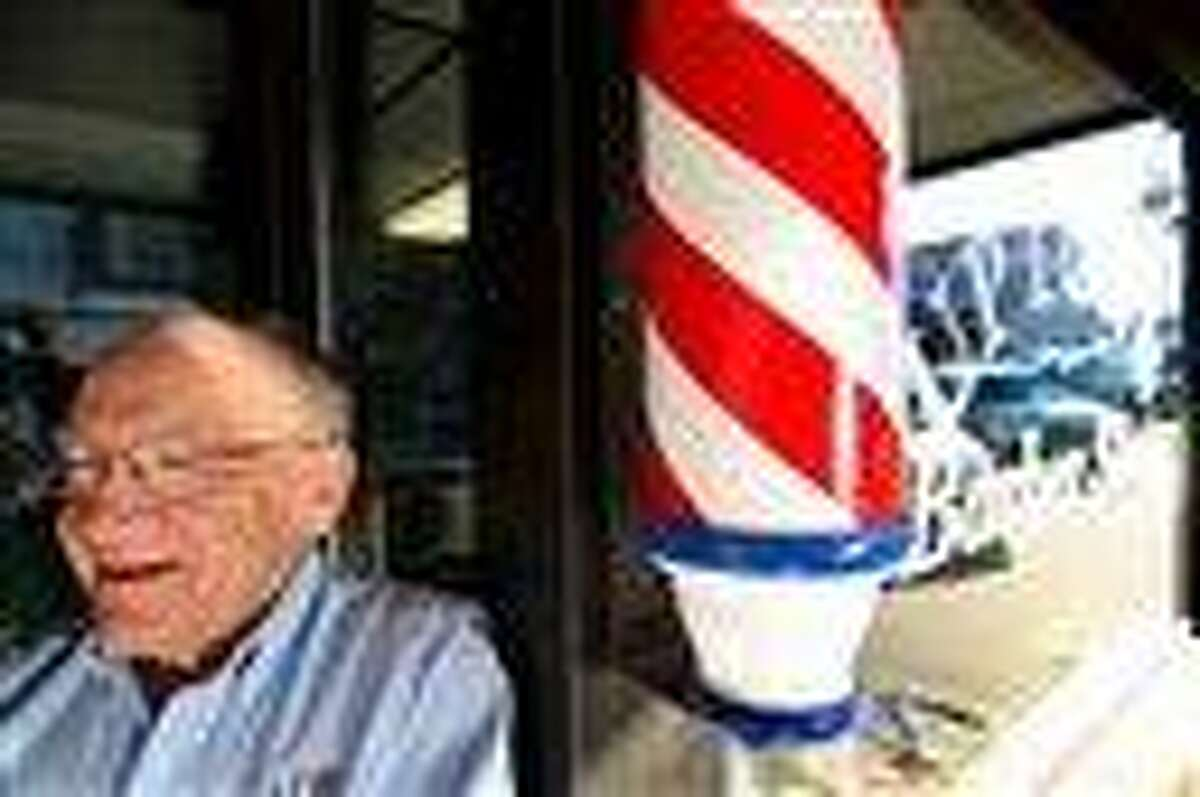 In this 2010 file photo, Howard Rettenmeier, who has cut hair for 55 years at the Uptown Barber Shop, stands by the barber pole at his Dyersville, Iowa, shop. The barber pole, one of the oldest signs that can be seen on storefronts across America, is an increasing source of friction between barbers and beauticians over which businesses get to display the iconic striped poles. Associated Press