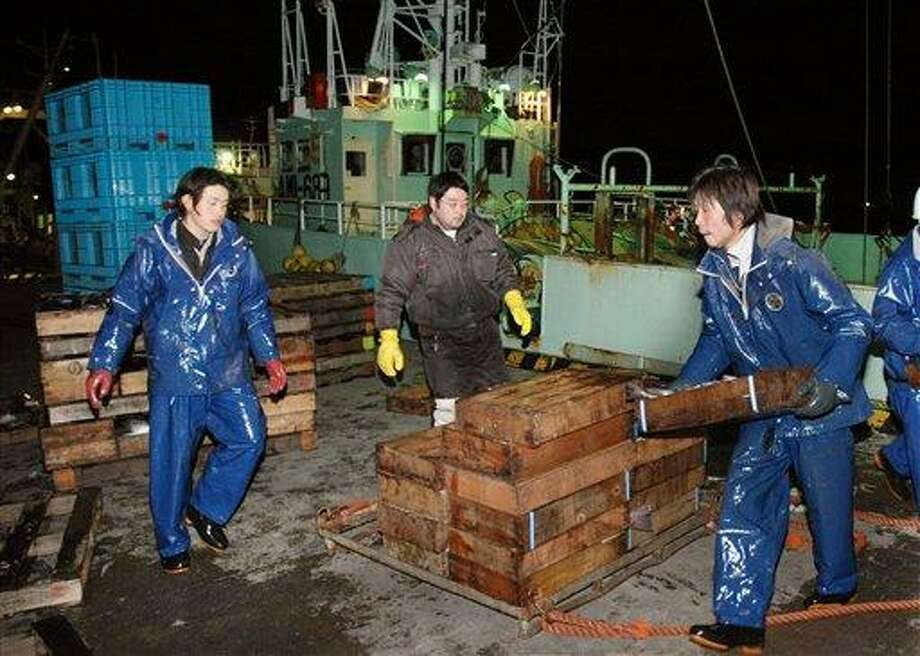Fishermen unload the day's catch from their fishing boat after a tsunami warning was lifted following an earthquake at a port in Hachinohe, Aomori Prefecture, northeastern Japan, Wednesday. A series of earthquakes rattled Tokyo and northeastern Japan late Wednesday evening but caused no apparent damage or injury in the same region hit by last year's devastating tsunami.  Associated Press Photo: AP / To-o Nippo Press via Kyodo News