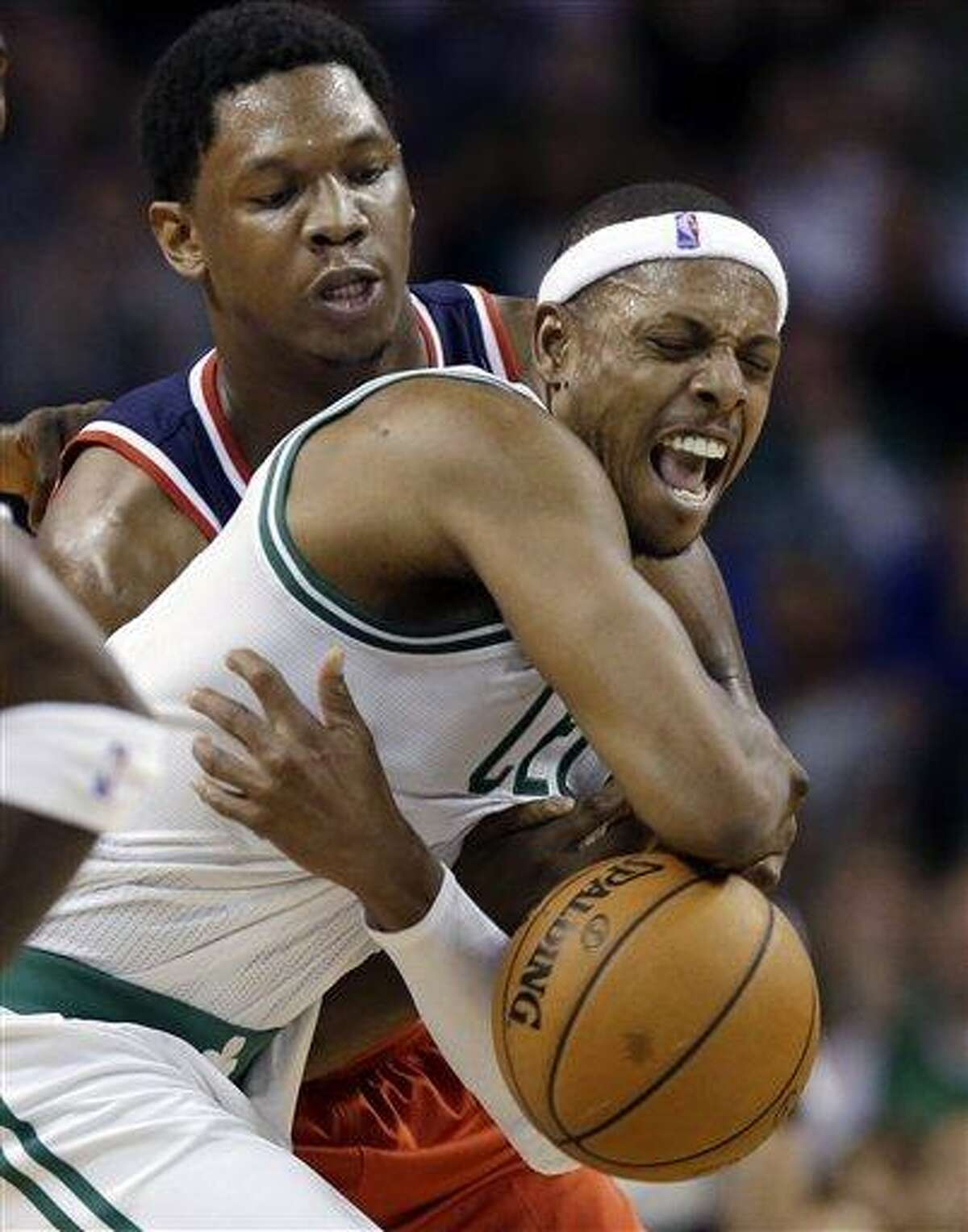 Boston Celtics forward Paul Pierce is grabbed and fouled from behind by Washington Wizards forward Kevin Seraphin after Pierce stole the ball from Seraphin during the second half of an NBA basketball game in Boston, Wednesday, Nov. 7, 2012. The Celtics won 100-94 in overtime. (AP Photo/Elise Amendola),