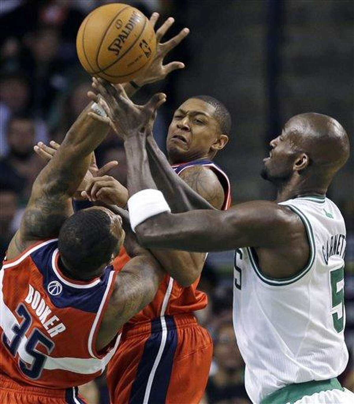 CORRECTS ID OF WIZARDS PLAYER AT MIDDLE TO BRADLEY BEAL, INSTEAD OF A.J. PRICE - Washington Wizards forward Trevor Booker (35) and guard Bradley Beal, middle, vie for a loose ball with Boston Celtics forward Kevin Garnett (5) during the first half of an NBA basketball game in Boston on Wednesday, Nov. 7, 2012. (AP Photo/Elise Amendola)