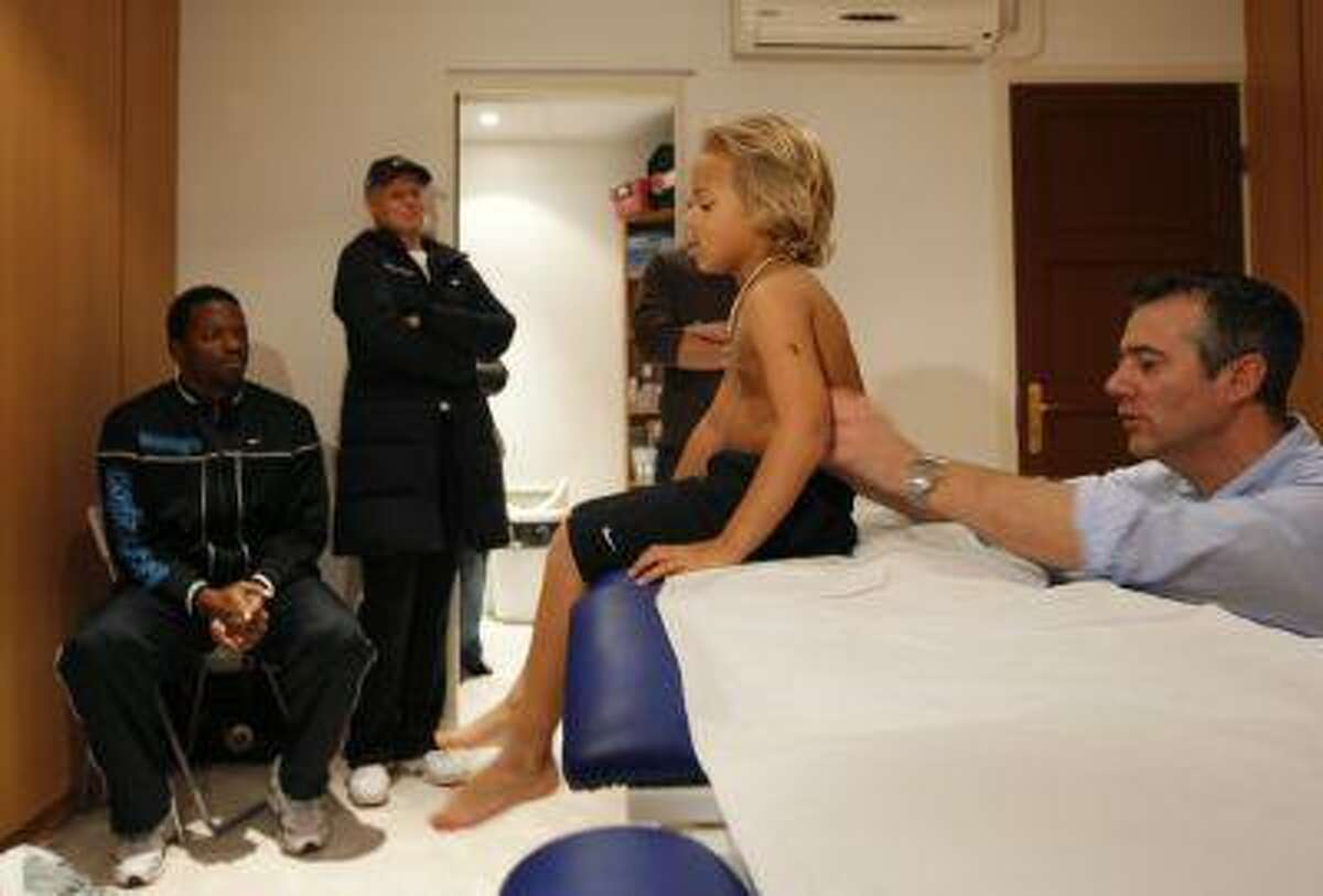 Jan Silva (2R), a five-year-old child from California, is examined by osteopath Francois Teissedre (R) during a medical check. The parents of Jan Silva, father Scott Silva (L) and mother Mari Maatanen (2L), look on. (REUTERS/Philippe Wojazer)