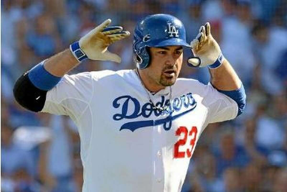 """After hitting a home run in the third inning of Game 5 of the NLCS at Dodger Stadium on Wednesday, Dodgers first baseman Adrian Gonzalez gestures with some Mickey Mouse ears in light of St. Louis pitcher Adam Wainwright's comment about Gonzalez's """"Mickey Mouse"""" celebration earlier in the series."""