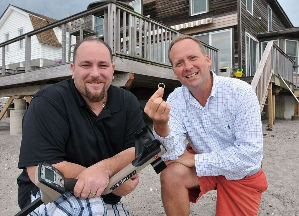 TJ Theodorsen shows off his wedding ring that was lost in the sand behind his Milford beach house and found by Andy Tkacs with his metal detector. Tkacs is the owner of New England Detectors, a Milford based company that sells metal detectors. Peter Casolino/New Haven Register