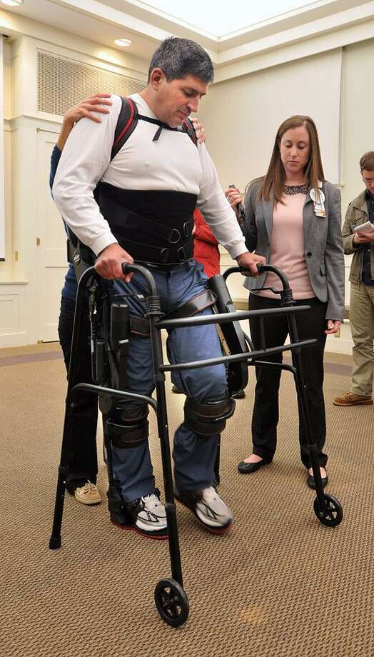 """Michael Loura, a patient at Gaylord Hospital, uses a EKSO wearable robotic exoskeleton to """"walk"""" with the help of physical therapists Erika Malits, right, and Erin Prastine, rear (hidden). Loura, who lost the use of his legs after being hit by a vehicle, has only used the EKSO 15-times, and is already making great strides, being able to stand and walk (with slight assistance). Peter Casolino/New Haven Register"""