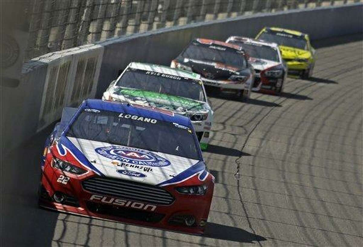 Joey Logano, Kyle Busch and Denny Hamlin, front to rear, battle in the early laps of the NASCAR Sprint Cup series auto race in Fontana, Calif., Sunday, March 24, 2013. Busch won. (AP Photo/Reed Saxon)