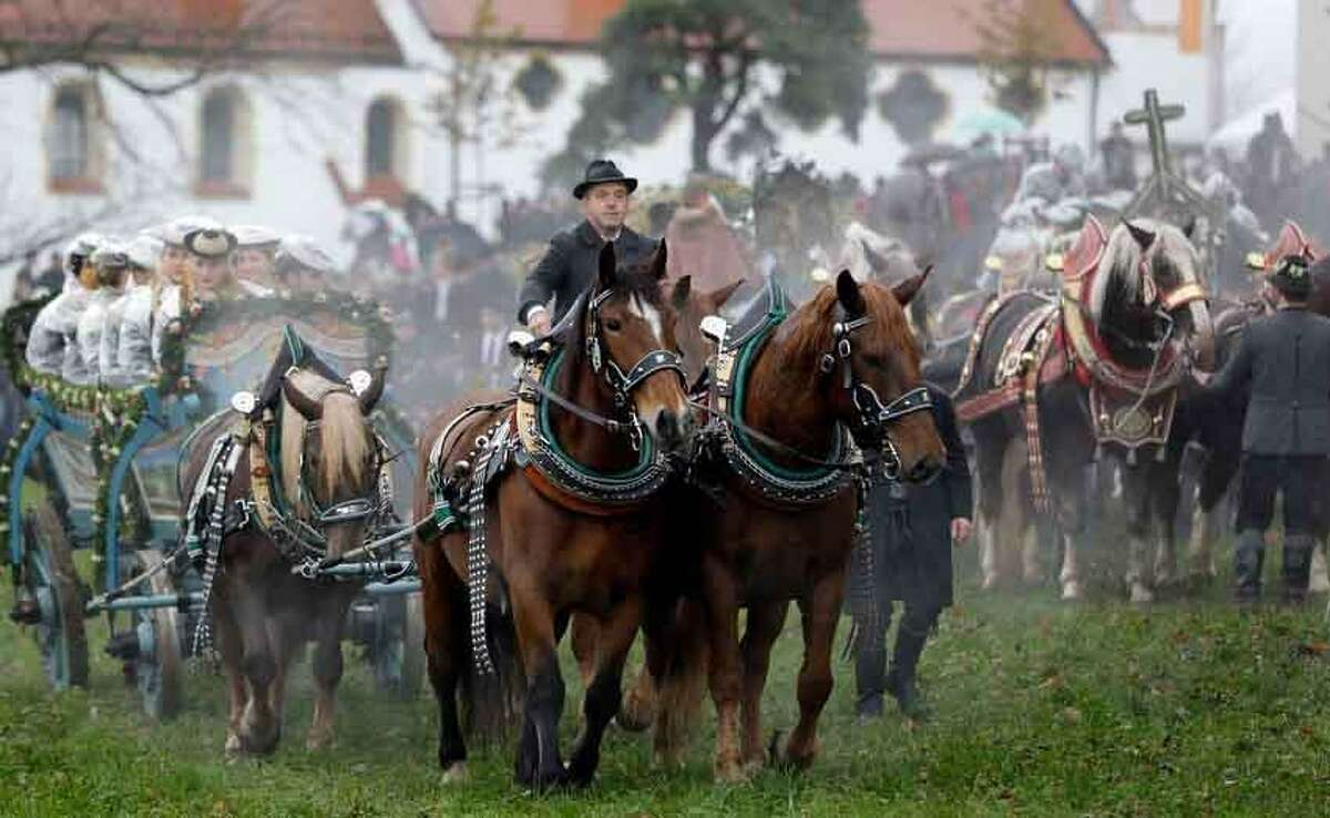 Horsemen steer their carriages over a rain-sodden meadow during the traditional Leonhardi pilgrimage in Bad Toelz, southern Germany, Tuesday, Nov. 6, 2012. The annual pilgrimage honors St. Leonhard, patron saint of the highland farmers for horses and livestock. (AP Photo/Matthias Schrader)