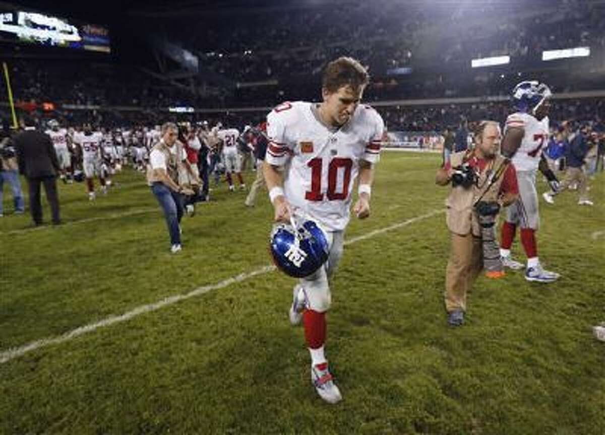 New York Giants quarterback Eli Manning (10) runs off the field after the Giants' 27-21 loss to the Chicago Bears in an NFL football game, Thursday, Oct. 10, 2013, in Chicago.