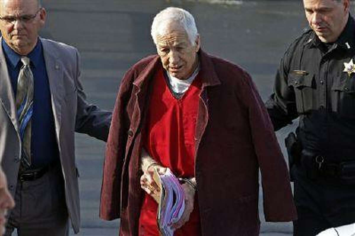 Former Penn State University assistant football coach Jerry Sandusky, center, leaves the Centre County Courthouse after attending a post-sentence motion hearing in Bellefonte, Pa., Thursday, Jan. 10, 2013.