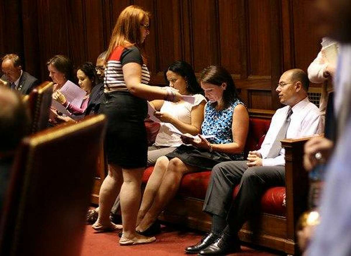 Newtown families get copies of the legislation in the Senate chamber as the bill is introduced after 1 a.m. Christine Stuart/CT News Junkie