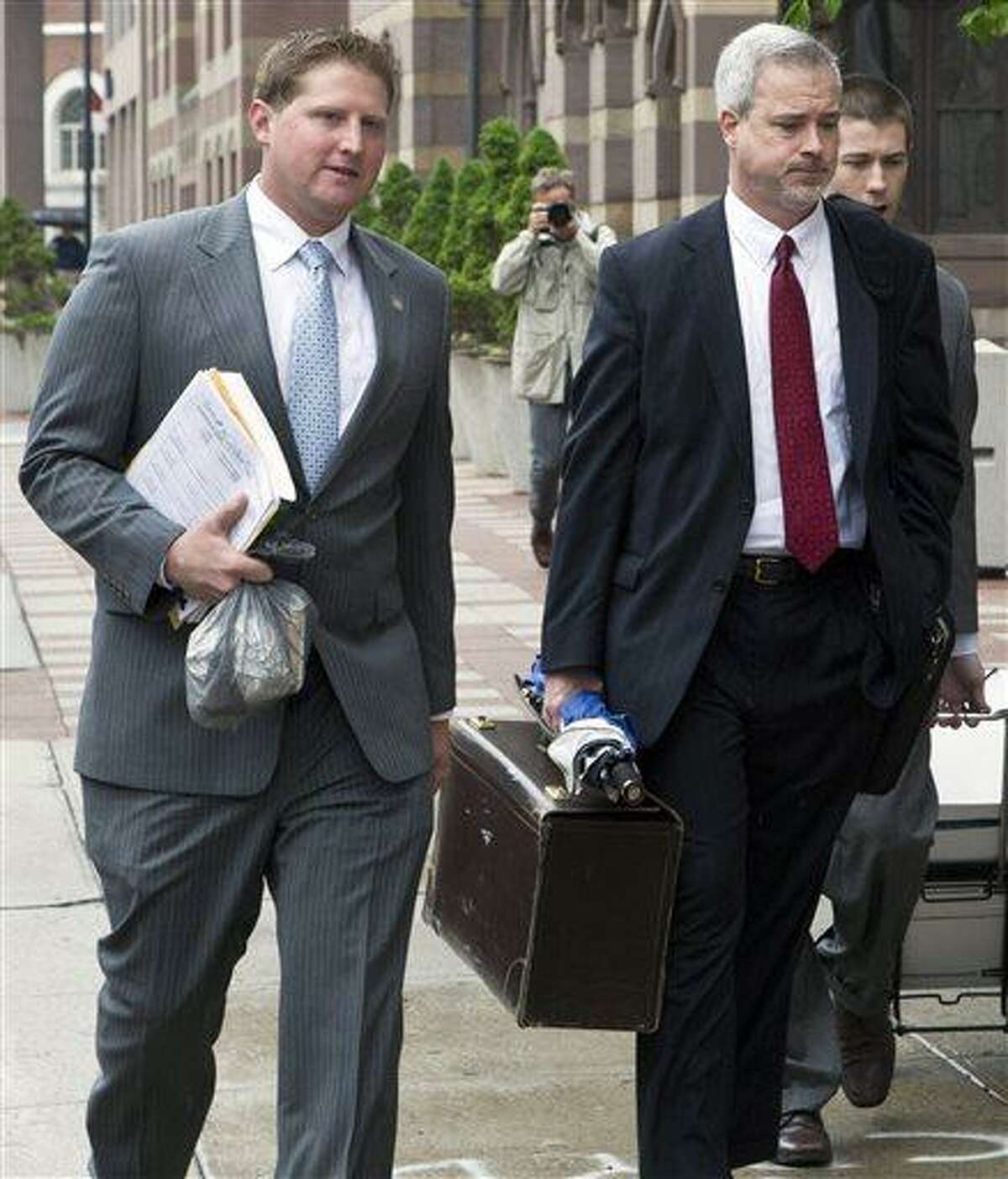 Meriden, Conn., police officer Evan Cossette, left, and his attorney Raymond Hassett arrive at the U.S. Courthouse in New Haven, Conn., Wednesday, May 29, 2013, for the second day of his trial. Cossette, the son of Meriden Police Chief Jeffry Cossette, is accused of brutality by shoving a handcuffed man in the police department lockup in 2010. (AP Photo/Record-Journal, Christopher Zajac)