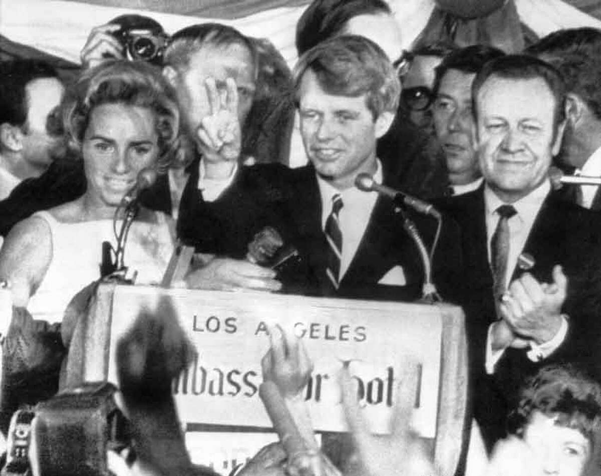 U.S. Sen. Robert F. Kennedy holds two fingers up in a victory sign as he talks to campaign workers at the Ambassador Hotel in Los Angeles, Ca., June 5, 1968. He is flanked by his wife Ethel, left, and his California campaign manager, Jesse Unruh, speaker of the California Assembly. After making the speech, Kennedy left the platform and was assassinated in an adjacent room. (AP Photo)