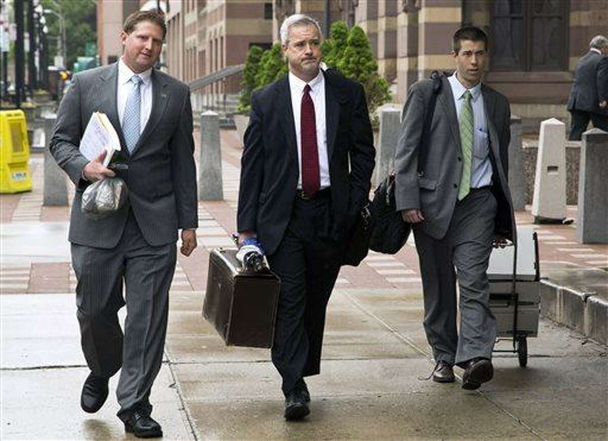 Meriden, Conn., police officer Evan Cossette, left, and his attorney Raymond Hassett, center, arrive at the U.S. Courthouse in New Haven, Conn., Wednesday, May 29, 2013, for the second day of his trial. Cossette, the son of Meriden Police Chief Jeffry Cossette, is accused of brutality by shoving a handcuffed man in the police department lockup in 2010. (AP Photo/Record-Journal, Christopher Zajac)