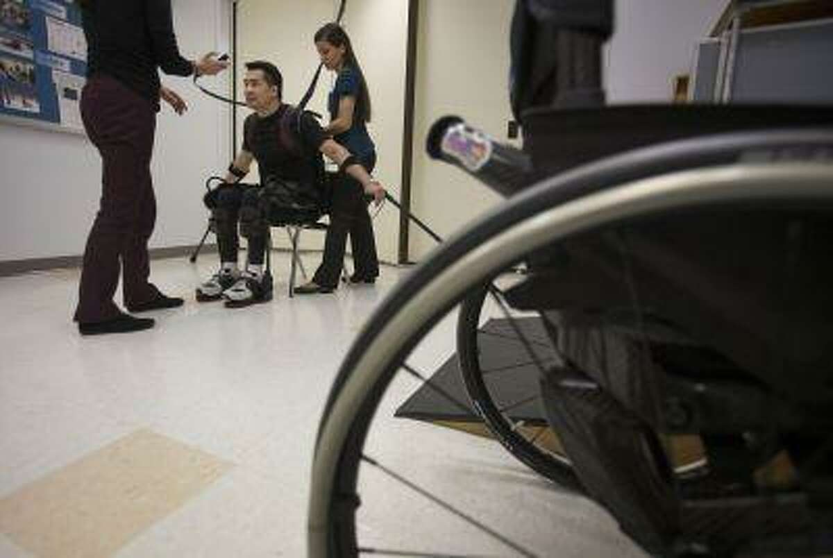 Robert Woo, 45. sits down onto a chair in an Ekso Bionics