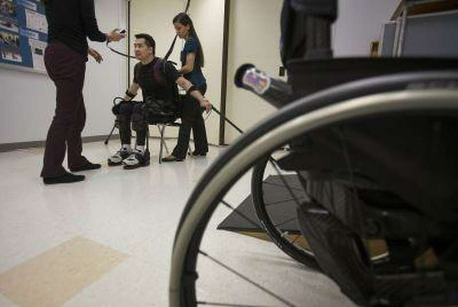 "Robert Woo, 45. sits down onto a chair in an Ekso Bionics ""exoskeleton,"" at Mount Sinai Medical Center in New York, U.S., on Thursday, March 14, 2013. (Scott Eells/Bloomberg)"