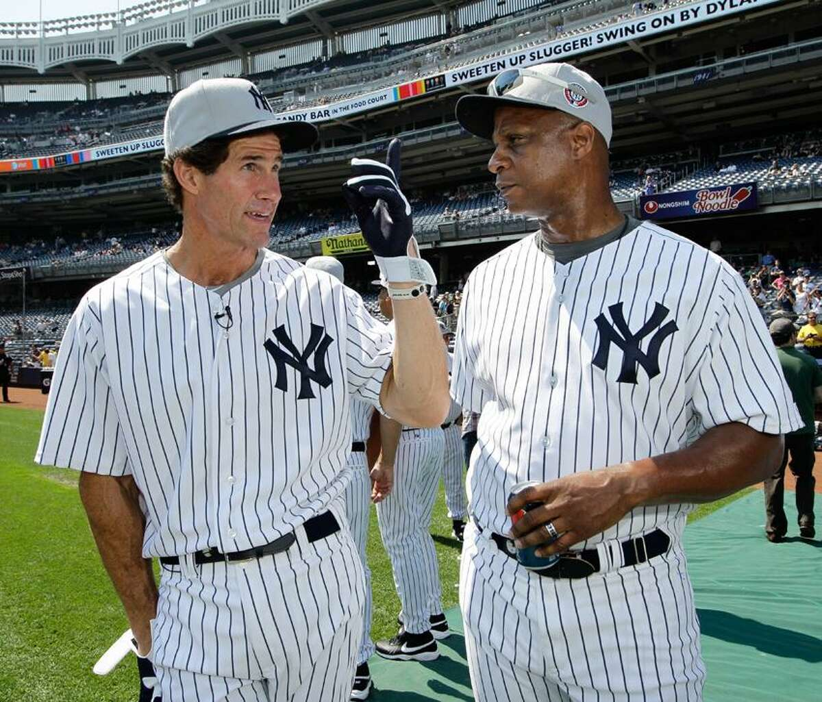 Former New York Yankees outfielders Paul O'Neill, left, and Darryl Strawberry talk on the field during Yankees Old Timers Day at Yankee Stadium in New York, Sunday, July 1, 2012. (AP Photo/Kathy Willens)