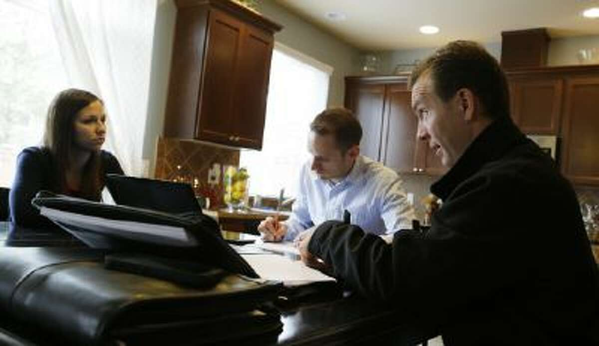 In this Thursday, Oct. 10, 2013 photo, insurance broker Jeff Lindstrom, right, meets with Brandi and Darren Litchfield to discuss health insurance plan options, at their home in the Seattle suburb of Bothell, Wash.