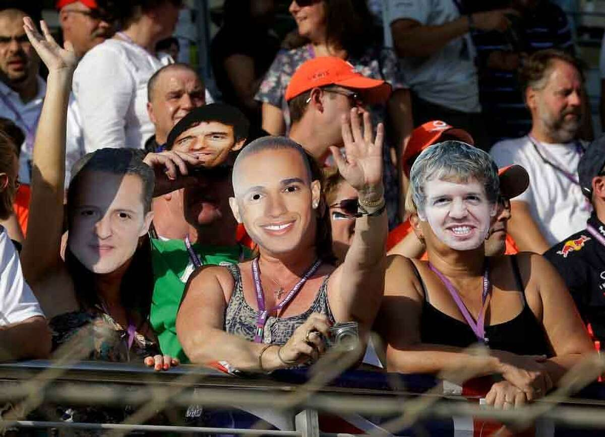 Spectarors wearing masks with pictures of Mercedes Grand Prix driver Michael Schumacher of Germany, left, McLaren Mercedes driver Lewis Hamilton of Britain and Red Bull driver Sebastian Vettel of Germany, wave from the stands prior to the start of the Emirates Formula One Grand Prix, at the Yas Marina racetrack, in Abu Dhabi, United Arab Emirates, Sunday, Nov. 4, 2012. (AP Photo/Luca Bruno)