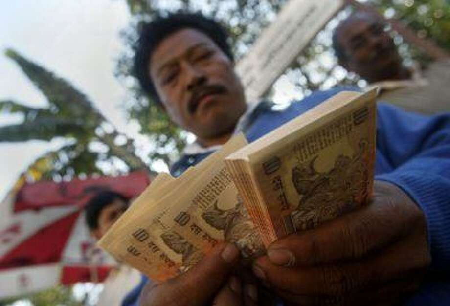 An Indian counts currency notes in front of the Reserve Bank of India in Gauhati, India, Tuesday, Nov. 22, 2011. (Anupam Nath/Associated Press)