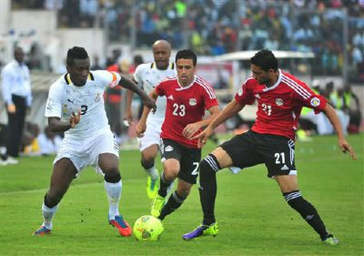 Ghana's Asamoah Gyan, left, battles with Egypt's Mohamed Naguib and Ahmed Shedid, right, during their World Cup playoff soccer match in Kumasi, Ghana, Tuesday, Oct. 15, 2013. Ghana stunned Egypt 6-1 in the first leg of their World Cup playoff on Tuesday, with Gyan's fifth-minute goal kicking off a dominant performance that makes the Black Stars overwhelming favorites to be one of the five African teams in Brazil next year.