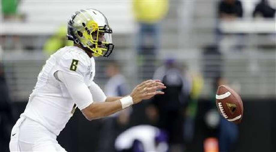 Oregon quarterback Marcus Mariota takes a snap before an NCAA college football game against Washington, Saturday, Oct. 12, 2013, in Seattle. Photo: AP / AP
