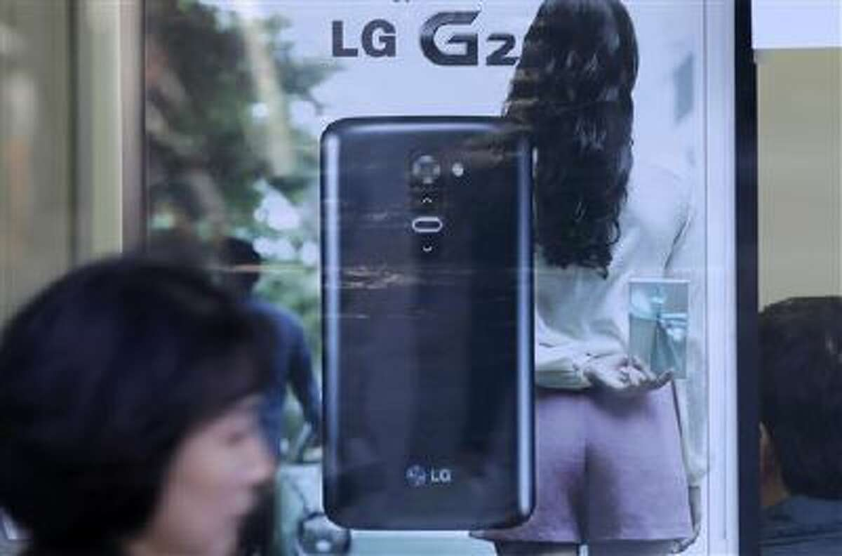 A woman walks by an advertisement of LG Electronics' smartphone G2 in Seoul, South Korea, Wednesday, Oct. 16, 2013.