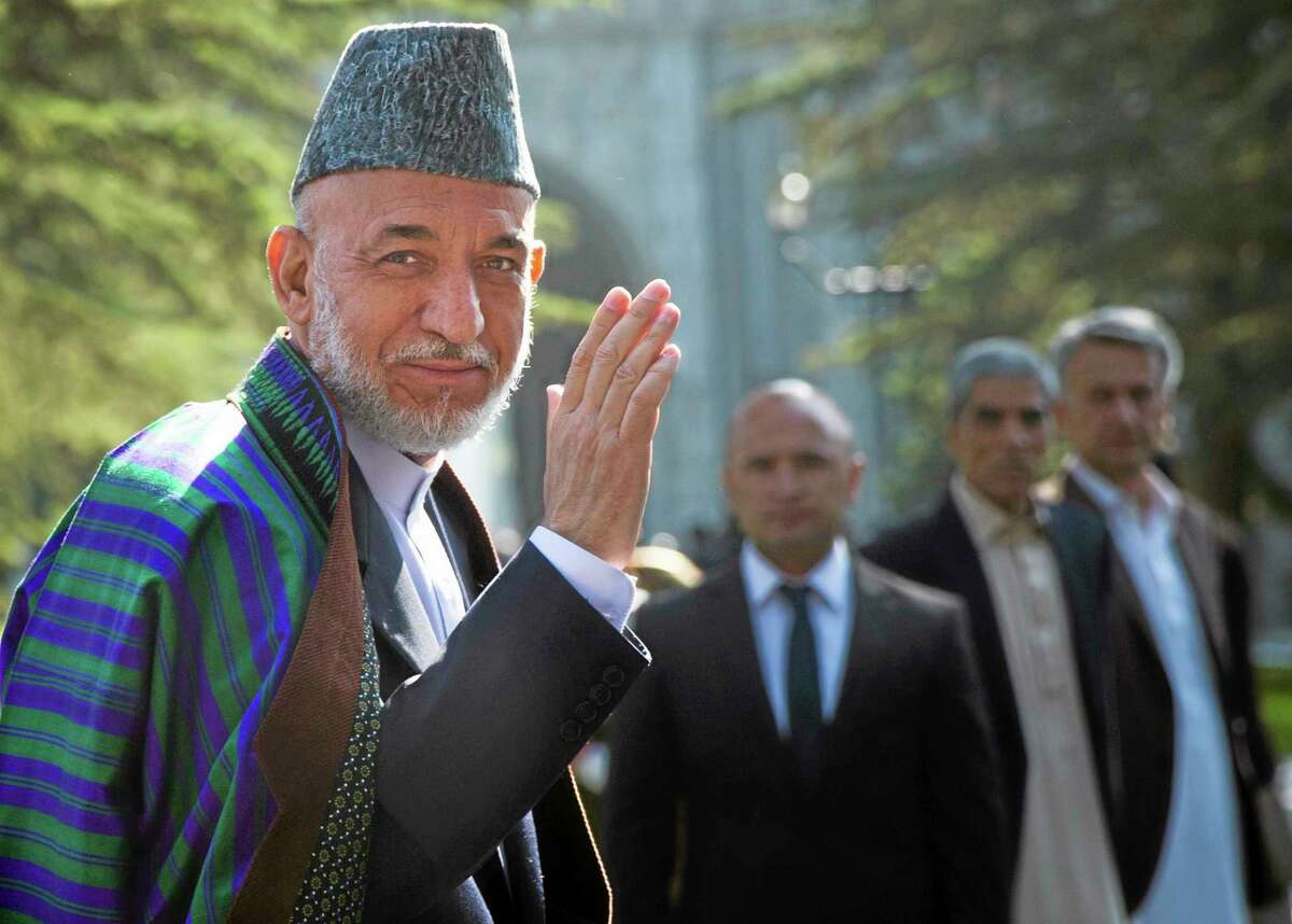 Afghan President Hamid Karzai arrives at a mosque inside the presidential palace to deliver his Eid al-Adha message, in Kabul, Afghanistan, Tuesday, Oct 15, 2013. The President urged the Taliban to lay down their weapons and to put an end to their fight. (AP Photo/Anja Niedringhaus)