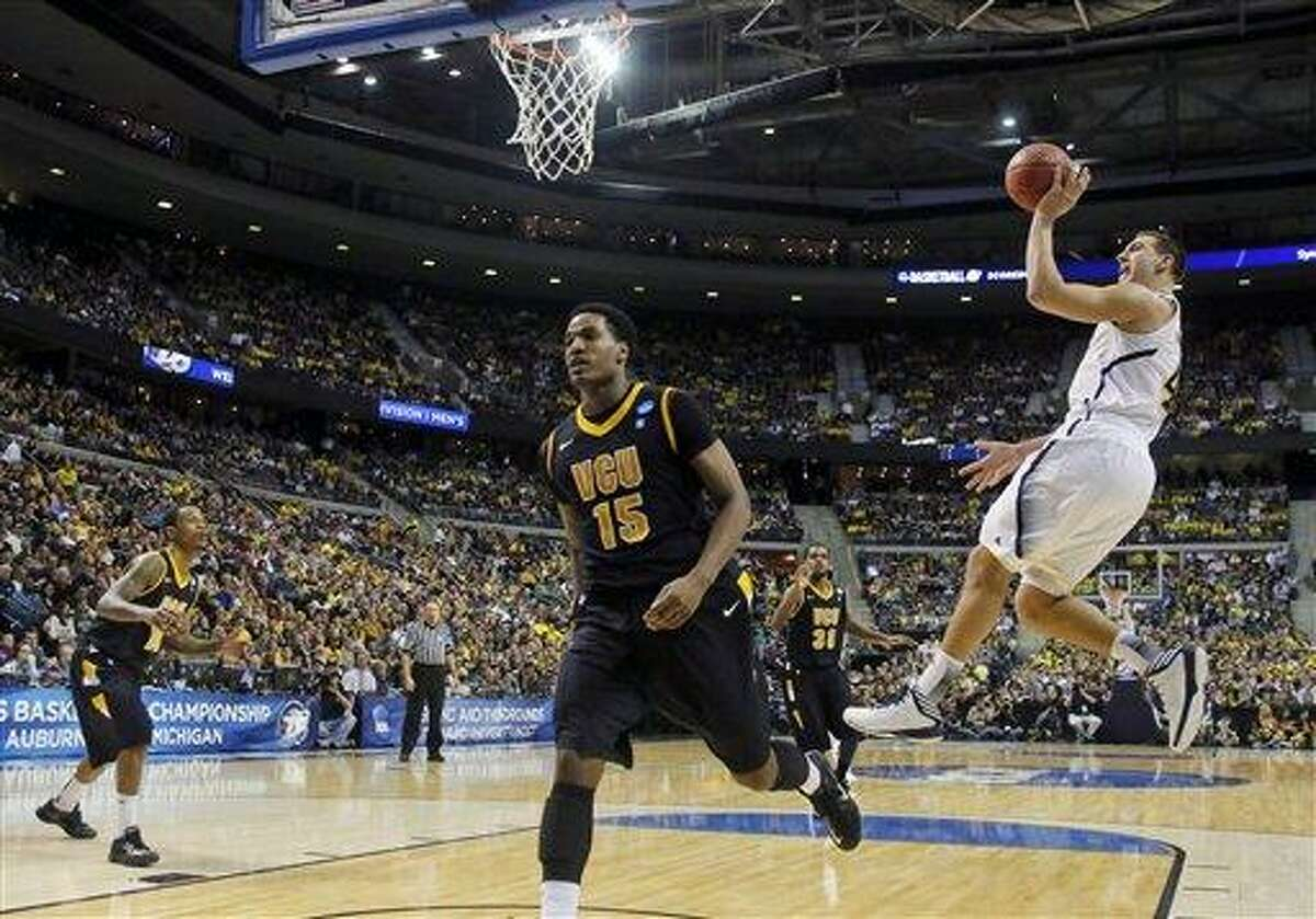 Michigan forward Mitch McGary (4) takes a shot as Virginia Commonwealth forward Juvonte Reddic (15) overruns the play in the second half of a third-round game of the NCAA college basketball tournament Saturday, March 23, 2013, in Auburn Hills, Mich. (AP Photo/Duane Burleson)