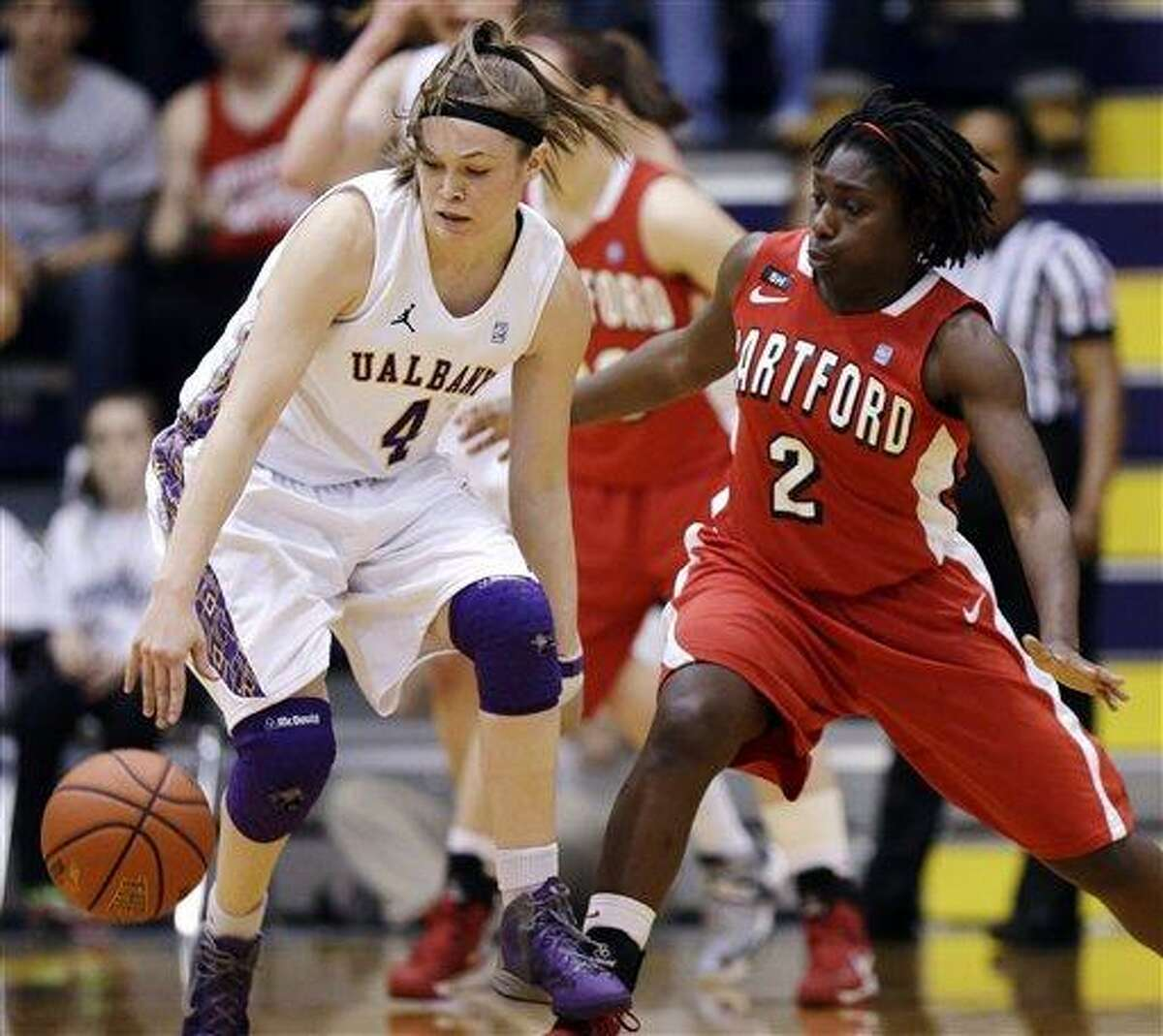 Albany guard Sarah Royals (4) holds off Hartford guard Daphne Elliott (2) during the first half of their NCAA college basketball game in the championship of the America East Conference tournament, Saturday, March 16, 2013, in Albany, N.Y. (AP Photo/Mike Groll)