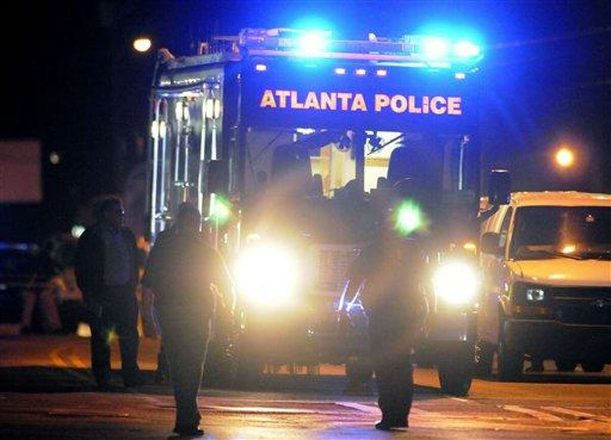 Law enforcement personnel investigate the scene of an Atlanta Police Department helicopter crash early Sunday that killed two officers aboard the aircraft. AP Photo/David Tulis